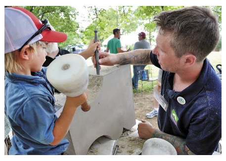 A child works with masonry tools under the guidance of a master carver.